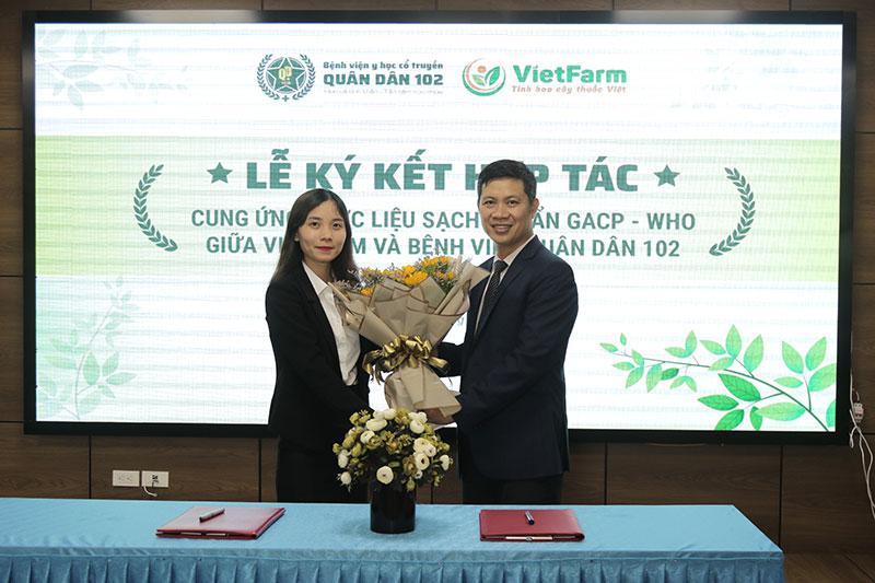 Đại diện Bệnh viện YHCT Quân Dân 102 tặng hoa cho đại diện Trung tâm Dược liệu Vietfarm
