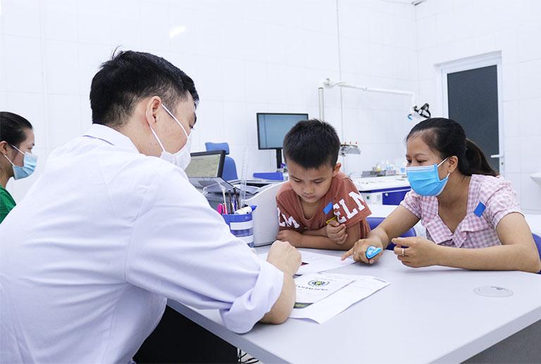 Bé Nguyễn Mạnh Cường và mẹ trong buổi tái khám tại Quân dân 102